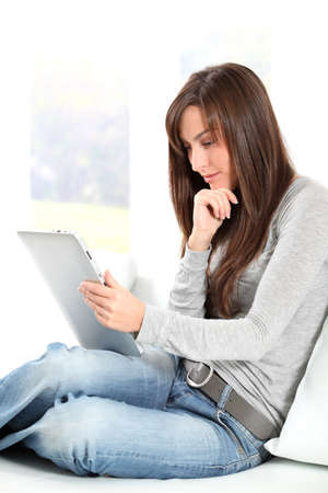 connexion: Young woman sitting on sofa with electronic pad Stock Photo