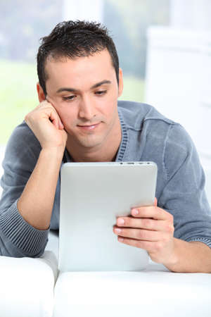 electronic pad: Young man sitting on sofa with electronic pad