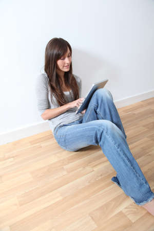 electronic pad: Young woman sitting on the floor with electronic pad