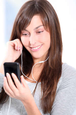 Closeup of young woman listening to music photo