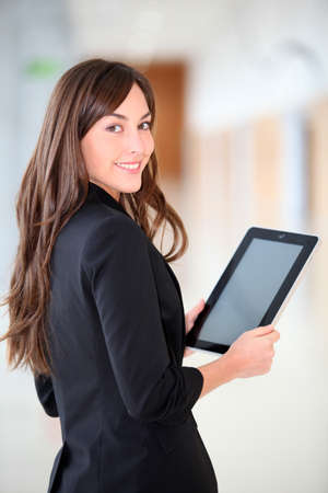 Businesswoman standing in hall with electronic pad photo