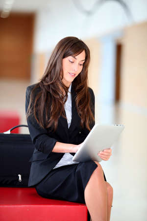 electronic pad: Businesswoman sitting in hall with electronic pad Stock Photo