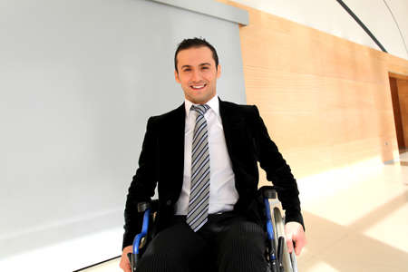 to attend: Businessman in wheelchair going to attend congress meeting Stock Photo