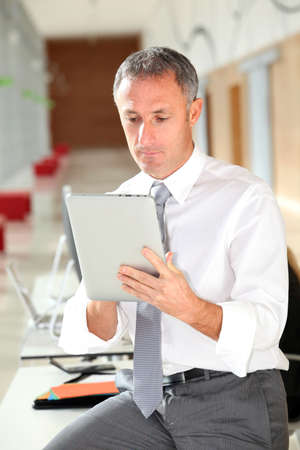 Office worker looking at internet on electronic pad photo