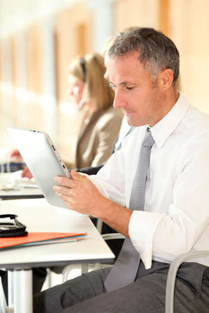 electronic pad: Office worker looking at internet on electronic pad Stock Photo