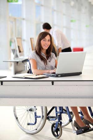 handicap: Businesswoman in sedia a rotelle, lavorando in ufficio