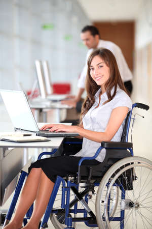 disabled person: Businesswoman in wheelchair working in the office