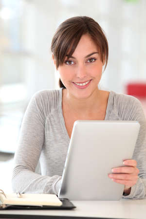 electronic pad: Beautiful businesswoman with electronic pad in the office
