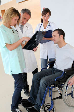 Medical team with handicapped person looking at X-ray photo