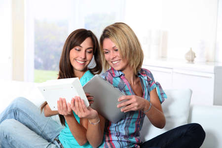 electronic pad: Girlfriends reading book on electronic pad