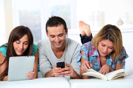 android tablet: Group of friends laying in sofa at home Stock Photo