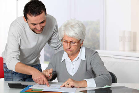 Young man helping elderly woman with paperwork Stock Photo - 8362762