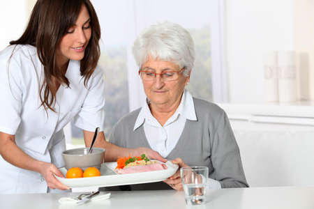Beautiful nurse bringing meal tray to old woman at nursing home Stock Photo - 8361075