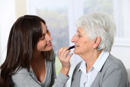 homecare: Young woman helping old woman to put makeup on Stock Photo