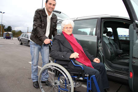 Young man assisting senior woman in wheelchair photo