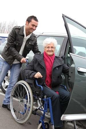 persona en silla de ruedas: Joven para ayudar a la mujer senior en silla de ruedas