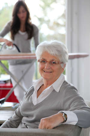 woman ironing: Closeup of elderly woman with home help Stock Photo