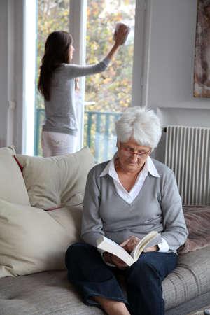 mujer leyendo libro: Anciana leyendo el libro mientras ama de llaves limpia ventanas