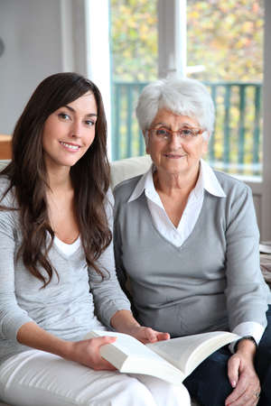 homecare: Young woman reading book to elderly woman