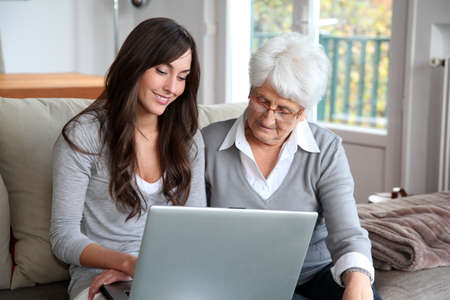 Young woman and elderly woman with laptop computer Stock Photo - 8375275
