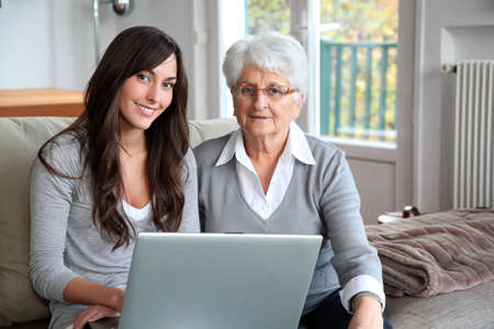 Young woman and elderly woman with laptop computer photo