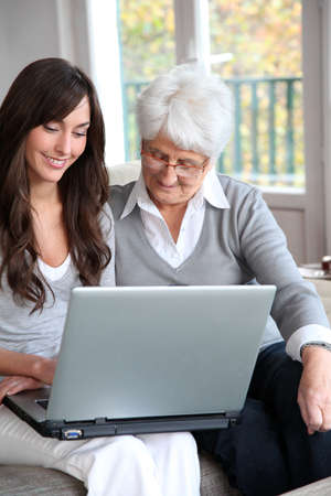 homecare: Young woman and elderly woman with laptop computer