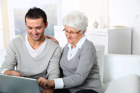 Elderly woman with young man using internet at home Stock Photo - 8375216