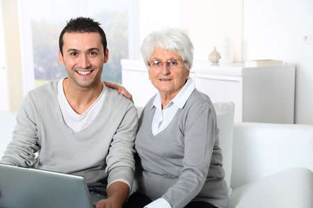 Elderly woman with young man using internet at home Stock Photo - 8374670
