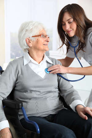 Elderly woman in wheelchair with nurse at home photo