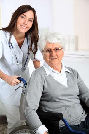 home health nurse: Elderly woman in wheelchair with nurse at home Stock Photo