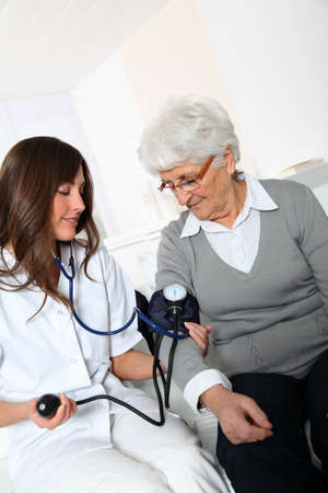 Closeup of nurse checking senior woman blood pressure photo