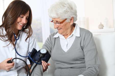 homecare: Closeup of nurse checking senior woman blood pressure
