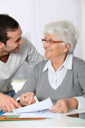 fill fill in: Young man helping elderly woman with paperwork Stock Photo
