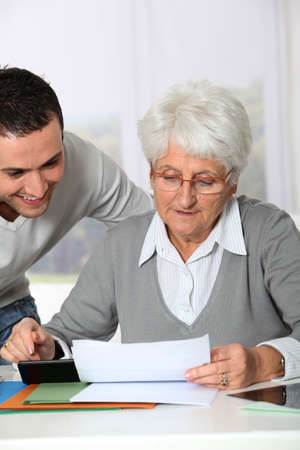 Young man helping elderly woman with paperwork photo