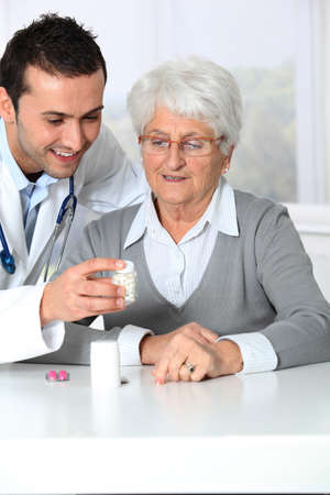 Doctor explaining drugs prescription to elderly woman photo