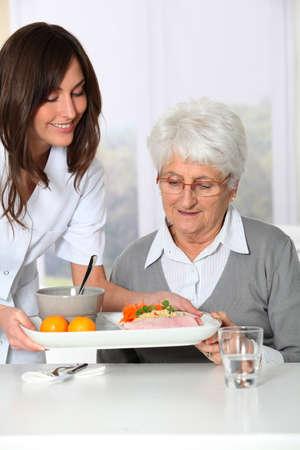 Beautiful nurse bringing meal tray to old woman at nursing home photo