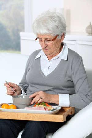 autonomia: Anciana sentado en el sof� con una bandeja de comida