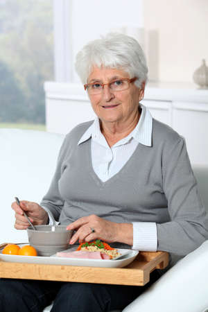 lunch tray: Elderly woman sitting in sofa  with lunch tray