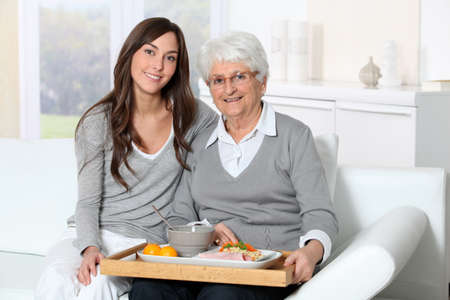 nursing assistant: Elderly woman and home carer sitting in sofa with lunch tray