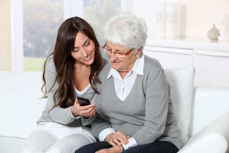Young woman showing how to use mobile phone to grandmother photo