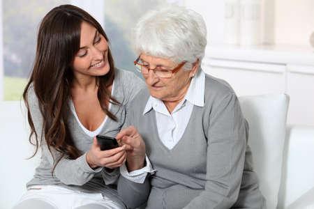 ama de llaves: Mujer joven que muestra c�mo utilizar el tel�fono m�vil para la abuela