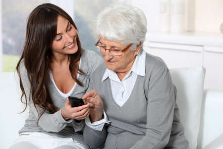 homecare: Young woman showing how to use mobile phone to grandmother