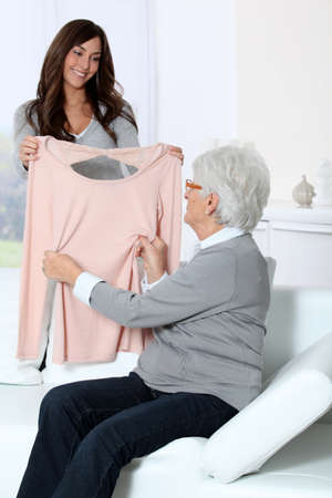 grandaughter: Young woman showing new clothes to grandmother
