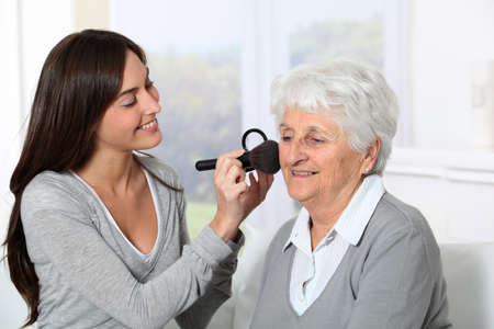 Young woman helping old woman to put makeup on Stock Photo - 8375282