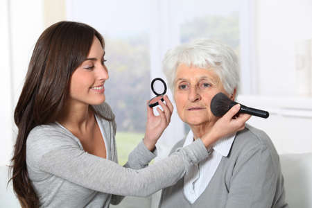 Young woman helping old woman to put makeup on photo