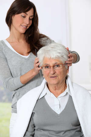 Young woman doing an haircut to old woman photo