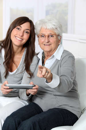 Young woman playing video game with grandmother photo