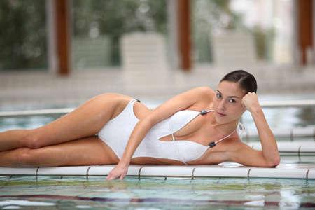 Beautiful woman laying by a thalassotherapy pool photo