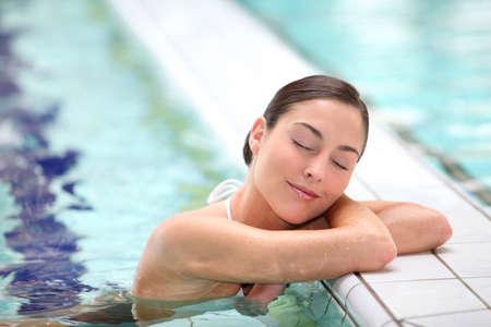Beautiful young woman relaxing in seawater pool  photo