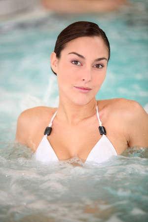 Beautiful young woman relaxing in seawater jacuzzi photo